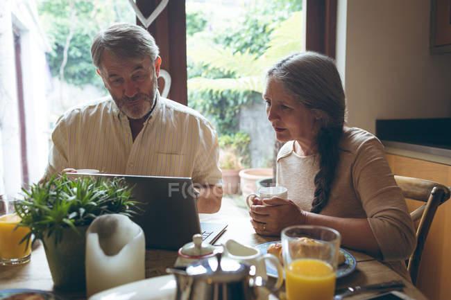 Coppia anziana che utilizza il computer portatile mentre prende il caffè a casa — Foto stock