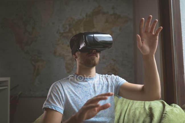 Homme utilisant casque de réalité virtuelle dans le salon à la maison — Photo de stock