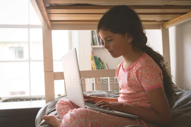 Seitenansicht von Mädchen mit Laptop auf dem Bett im Schlafzimmer zu Hause — Stockfoto