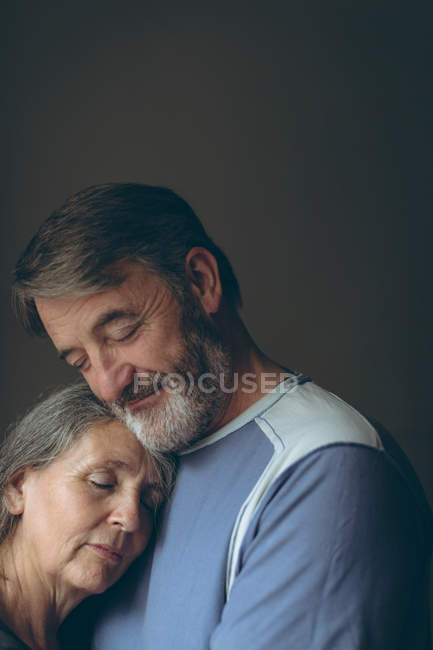 Romantic senior couple embracing each other at home — Stock Photo