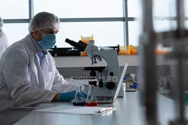Male scientist using microscope in laboratory — Stock Photo