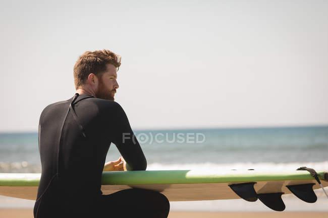 Серфер с доской для серфинга, сидящий на пляже в солнечный день — стоковое фото