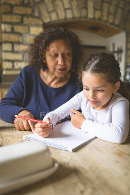 Grandmother helping her granddaughter in studies at home — Stock Photo