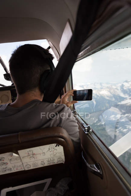 Pilot taking photos with mobile phone while flying in aircraft cockpit — Stock Photo