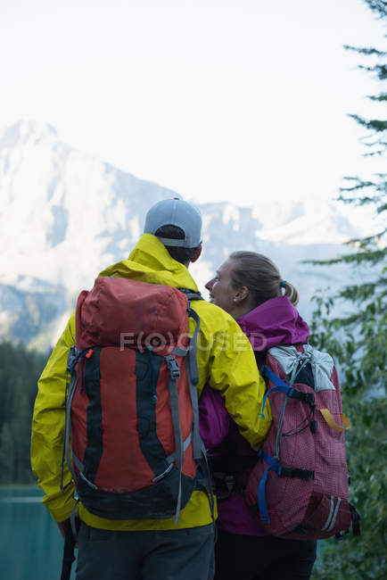 Rear view of couple standing with backpack in mountains — Stock Photo
