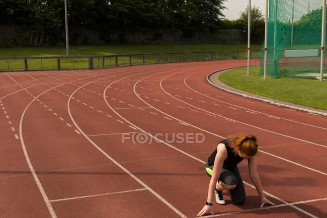 Молодая спортсменка готова бегать по беговой дорожке — стоковое фото