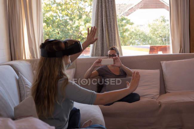 Женщина с помощью гарнитуры виртуальной реальности и ее партнер щелкает фото с мобильного телефона дома — стоковое фото