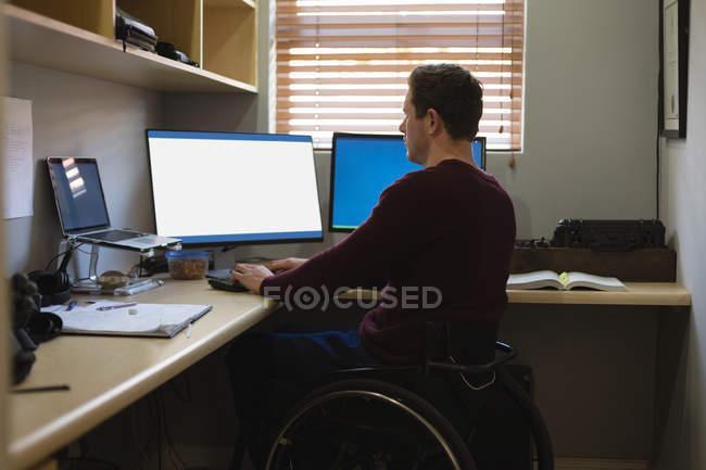 Handicapés travaillant sur ordinateur à domicile — Photo de stock