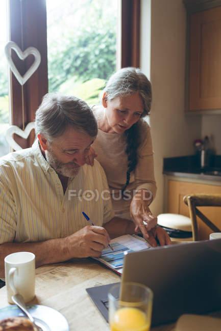 Älteres Paar prüfen Rechnungen zu Hause — Stockfoto