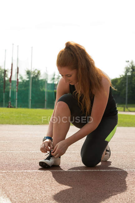 Young female athletic tying shoe laces on a running track — Stock Photo