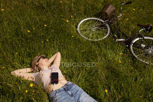 Woman listening music on mobile phone in the field — Stock Photo