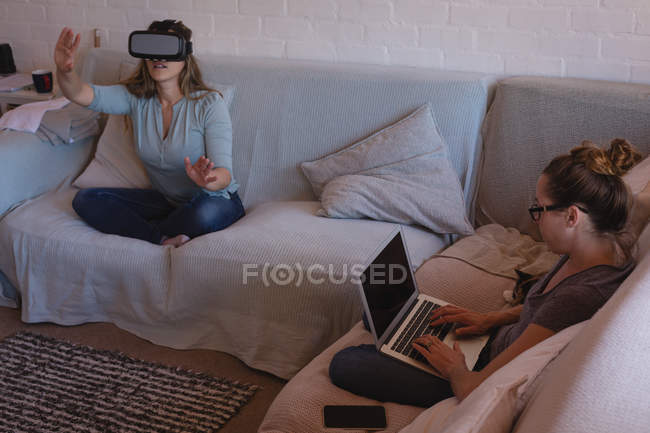 Lesbian couple using virtual reality headset and laptop on sofa at home — Stock Photo