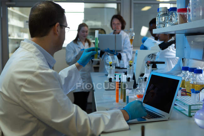 Male scientist using laptop while holding test tube in laboratory — Stock Photo