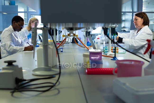 Científicos experimentando juntos en laboratorio - foto de stock