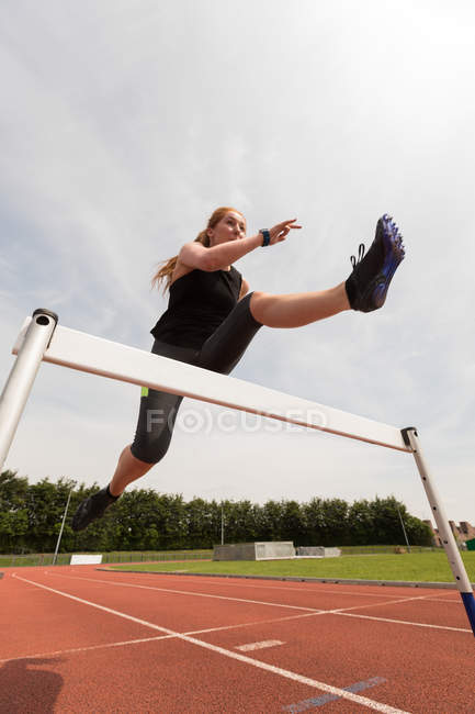 Female athletic jumping over hurdle on sports track — Stock Photo