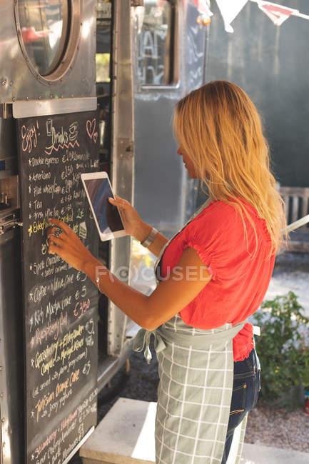 Beautiful female waitress writing menu on menu board while using digital tablet — Stock Photo
