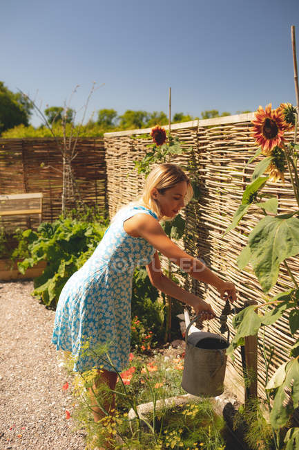 Woman filling water in the watering can at garden — Stock Photo