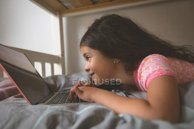 Nahaufnahme von Mädchen mit Laptop auf dem Bett im Schlafzimmer zu Hause — Stockfoto
