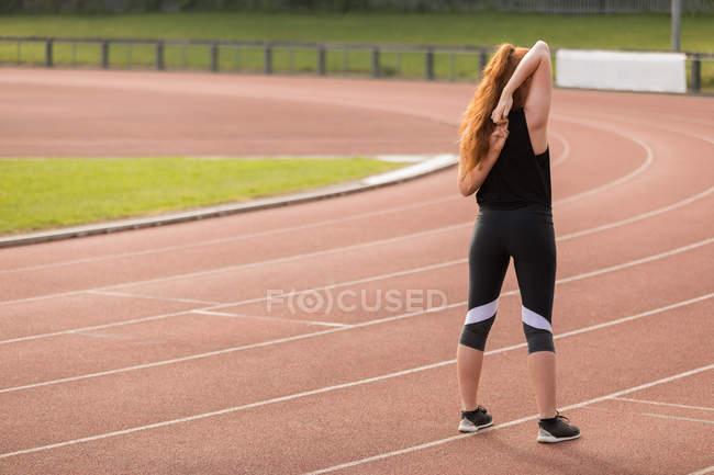 Visão traseira do exercício atlético feminino na pista de corrida — Fotografia de Stock