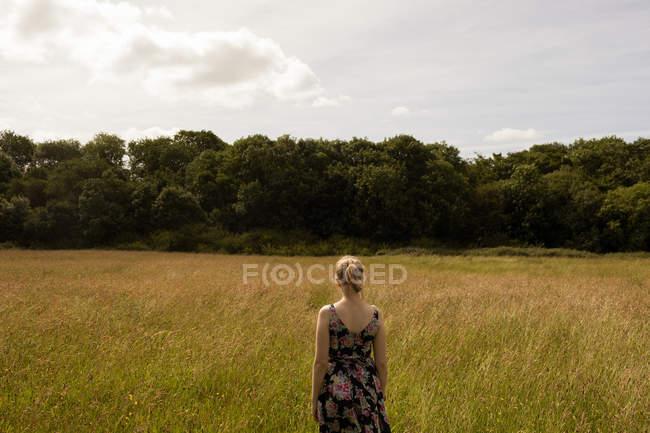 Mulher pensativa em pé no campo — Fotografia de Stock