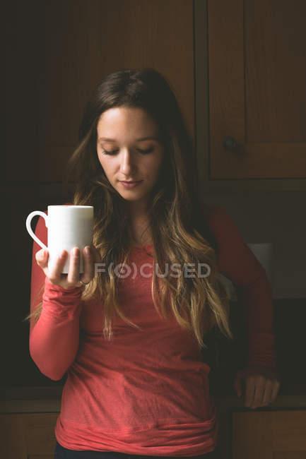 Женщина с кофейной кружкой на кухне дома — стоковое фото