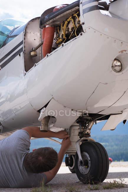 Инженер, Обслуживание шасси возле ангара — стоковое фото