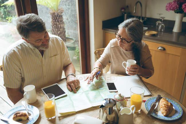 Casal sênior discutindo sobre um mapa em casa — Fotografia de Stock