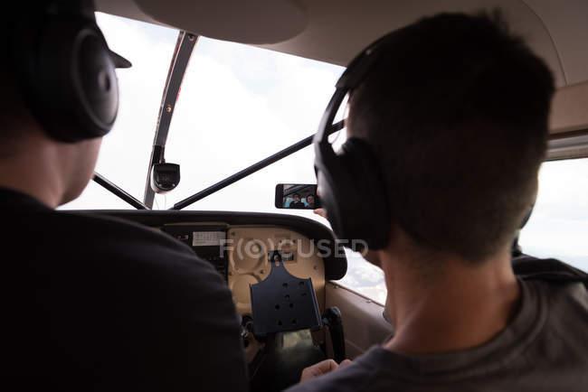 Pilotes prenant selfie avec téléphone portable alors qu'il volait dans le cockpit de l'avion — Photo de stock