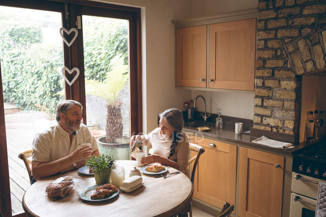 Senior couple having breakfast in kitchen at home — Stock Photo