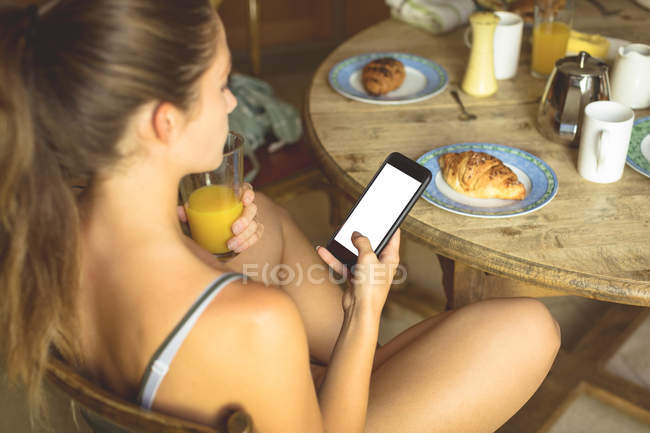 Женщина с помощью мобильного телефона на обеденный стол у себя дома — стоковое фото