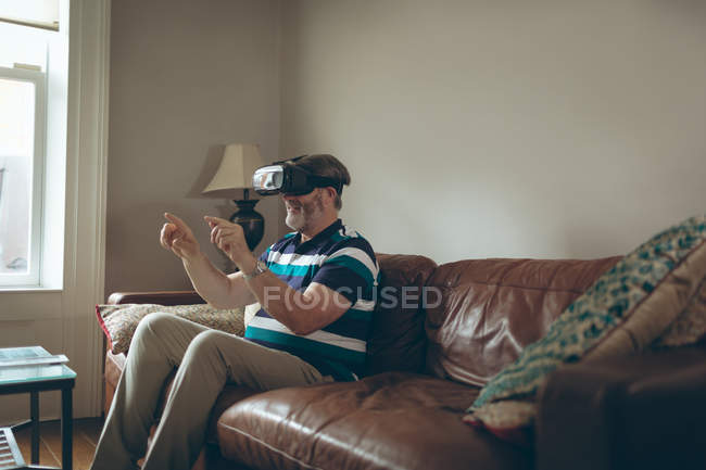 Senior man using virtual reality headset in living room at home — Stock Photo