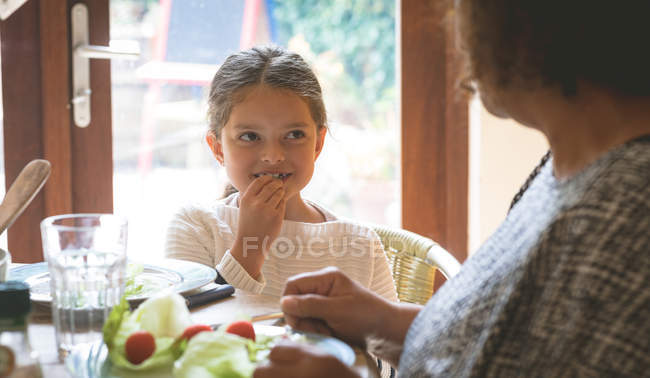 Grandmother and granddaughter having a meal on dining table at home — Stock Photo