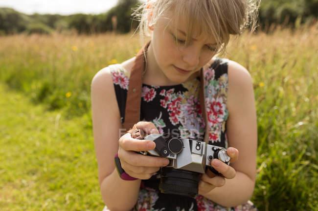Donna che rivede le foto sulla macchina fotografica sul campo — Foto stock