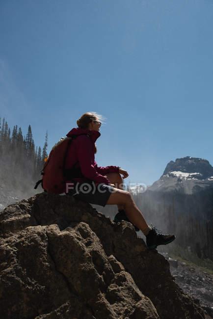 Женщины турист расслабляющий на скале в горах — стоковое фото