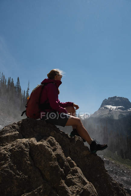 Female hiker relaxing on a rock in mountains — Stock Photo