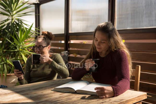 Couple lesbien prenant un café tout en utilisant un téléphone mobile et un livre de lecture à la maison — Photo de stock