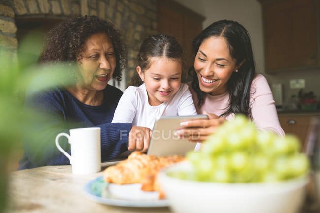 Happy family using digital tablet at home — Stock Photo
