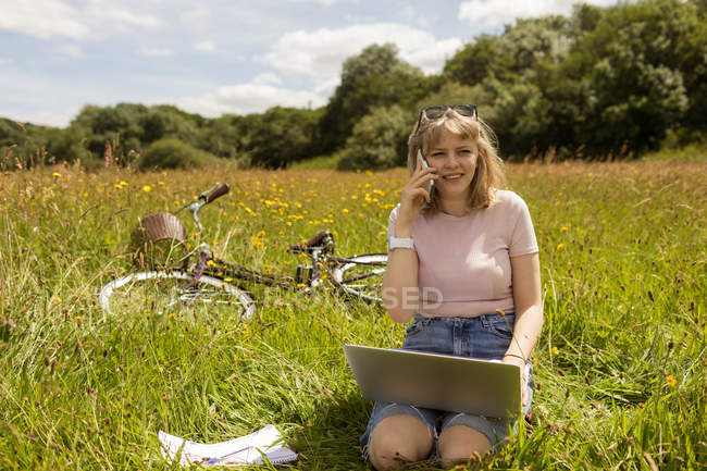 Woman talking on mobile phone while using laptop in the field — Stock Photo