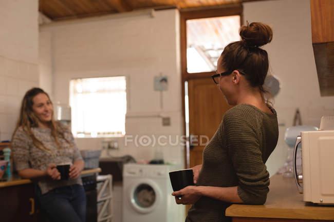 Coppia lesbica con tazza di caffè che interagisce tra loro in cucina a casa — Foto stock