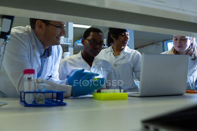 Equipe de cientistas experimentar juntos no laboratório — Fotografia de Stock