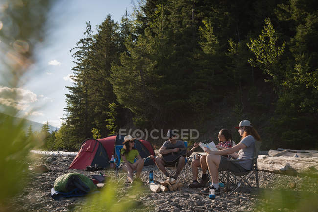 Group of hikers camping near riverside — Stock Photo
