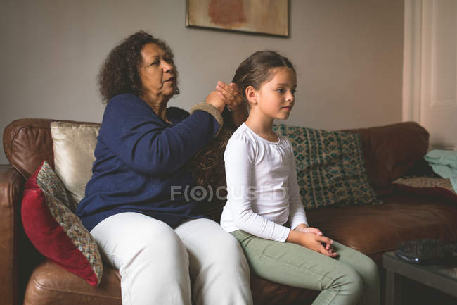 Grandmother is making hairstyle of granddaughter at home — Stock Photo