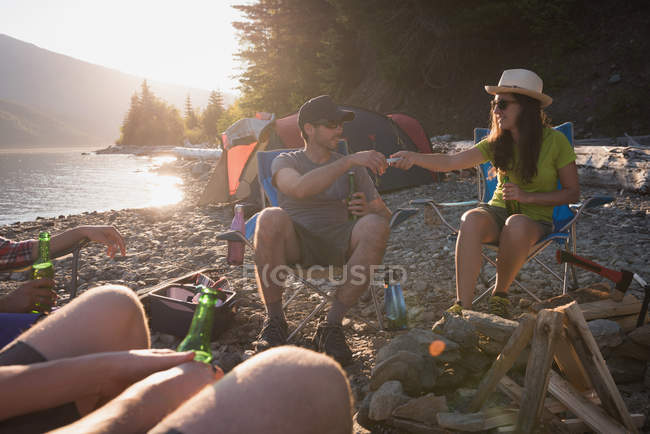 Group of friends camping near riverside on a sunny day — Stock Photo