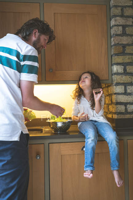 Vater interagiert mit seiner Tochter beim Gemüsewaschen in der heimischen Küche — Stockfoto
