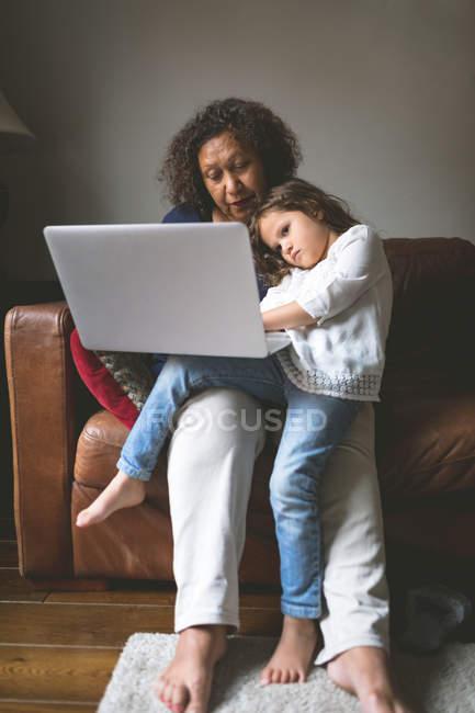 Маленькая девочка, используя ноутбук с бабушкой на диване у себя дома — стоковое фото