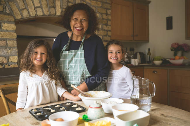 Grandmother standing with her granddaughters in kitchen at home — Stock Photo