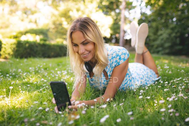 Frau macht Selfie mit Handy im Park — Stockfoto