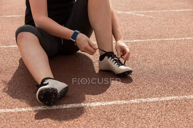 Low section of female athletic tying shoe laces on a running track — Stock Photo