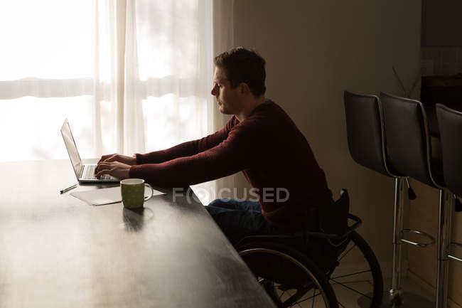 Disabled man using laptop on dinning table at home — Stock Photo