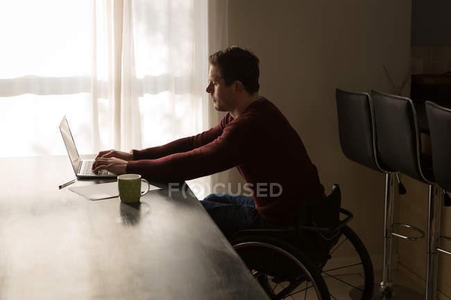 Инвалид использует ноутбук на обеденном столе дома — стоковое фото